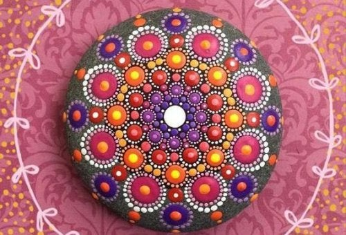 A colorful mandala painted on a rock.