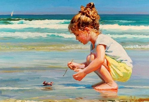 A little girl playing with a crab at the beach.
