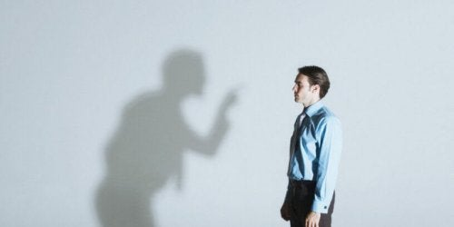 A businessman being scolded by a shadow.
