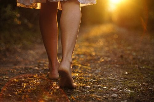 A woman walking barefoot on a path outside.
