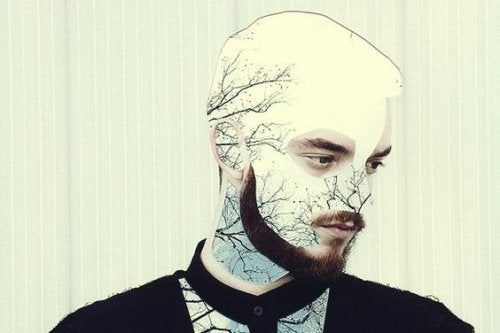 man with his face changed with paper cutouts of white scenery and trees
