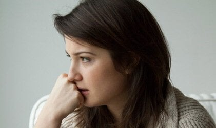 A woman with her hand on her chin. looking worried.