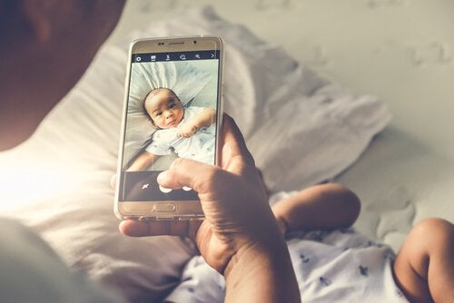 sharenting: a father taking a photo of his baby