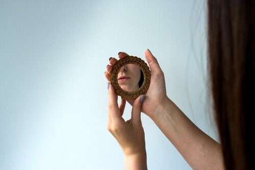 A picture showing someone holding a small hand mirror with a reflection of a corner of their face.