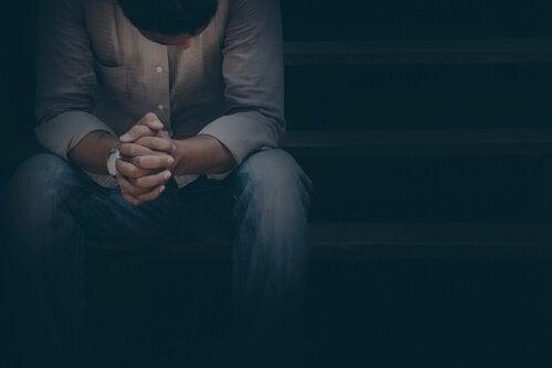 A man sitting down in the dark, feeling guilty.