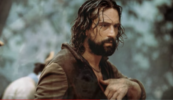 A still from The Mission showing Robert DeNiro holding his hand to his chest.