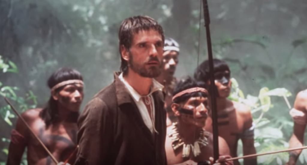 A still from the movie showing Jeremy Irons with a group of native people behind him.