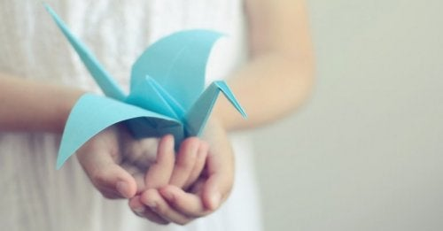 A person holding a blue paper bird.