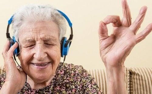 older woman listening to music with blue headphones