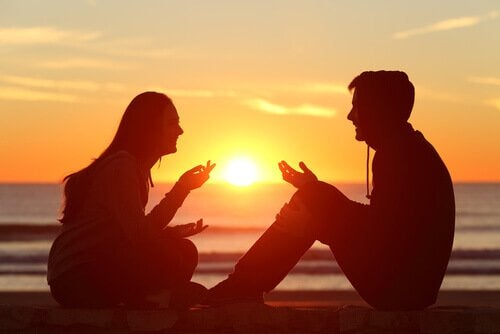 A couple talking at a beach at sunset.