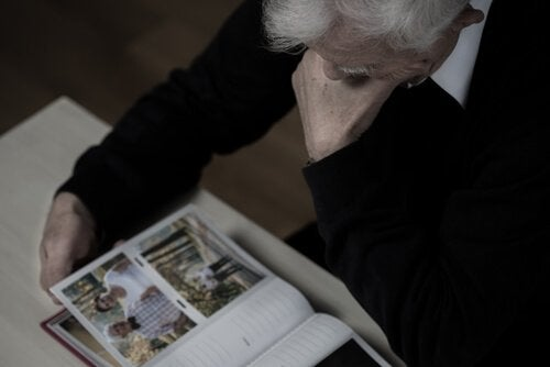 An older person looking at photographs.