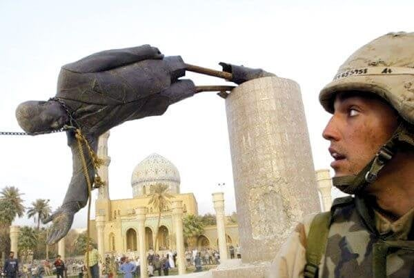 A picture showing a large group of people tearing down the statue of Saddam Hussein, while a US soldier looks on.