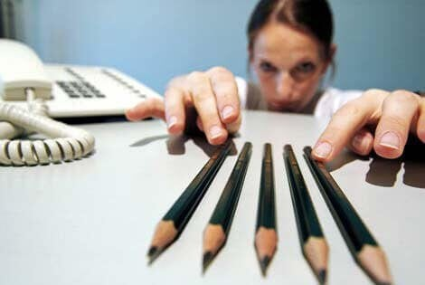 A woman sitting at her desk and meticulously ordering her pencils into a straight line.