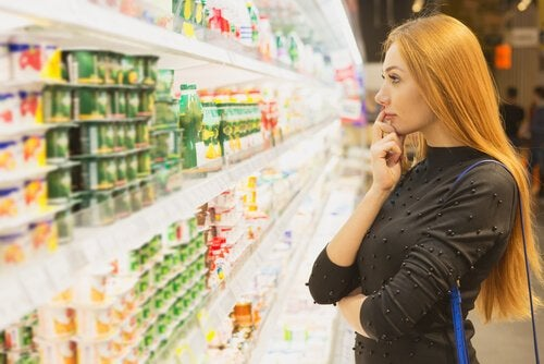 A woman deciding what to buy at the supermarket.