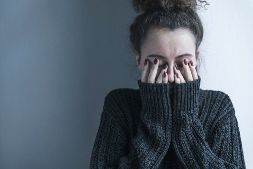A frustrated woman covering her face representing destigmatizing mental illness