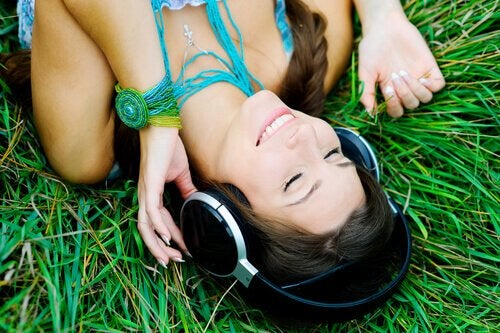 a woman lying on the grass listening to music
