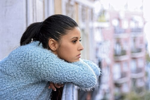 A woman on a balcony looking pensive.