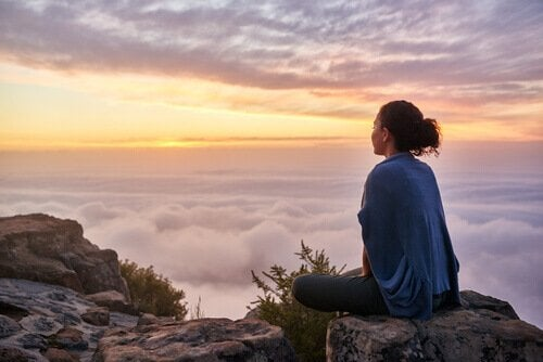 a woman sitting on top of a mountain practicing the concept of value your effort