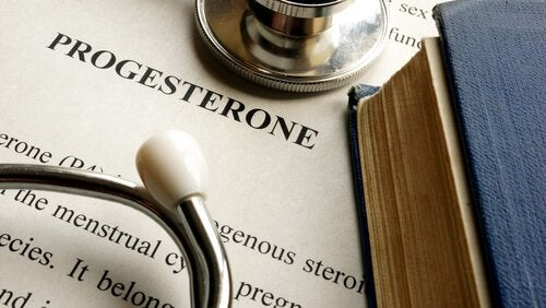 A close-up picture showing the word progesterone printed on a sheet of paper lying under a stethoscope.