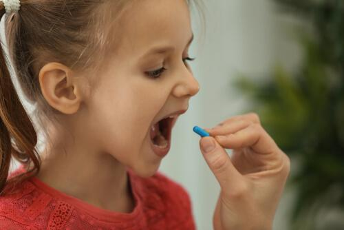 A child opening their mouth wide to take a pill.