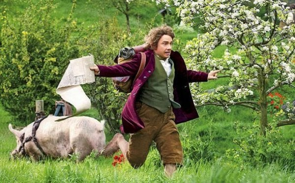 A still image from the movie showing Bilbo Baggins (played by Martin Freeman) running through a field with papers in his hand.