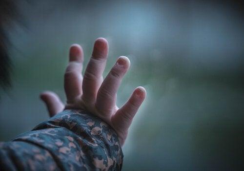 A boy's hand on the window pane.
