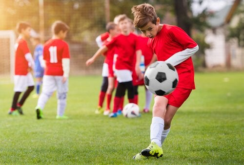 A boy in a youth soccer team kicking a ball.