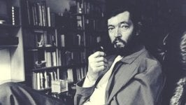 A picture shows Julio Cortázar sitting in a chair with a pipe in his hand, looking at the camera.
