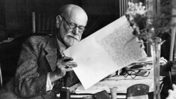 Sigmund Freud examining a paper.