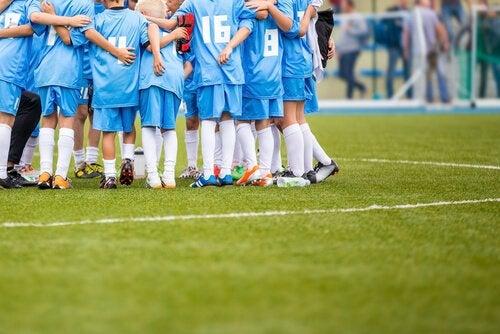 A youth soccer team hudling together.