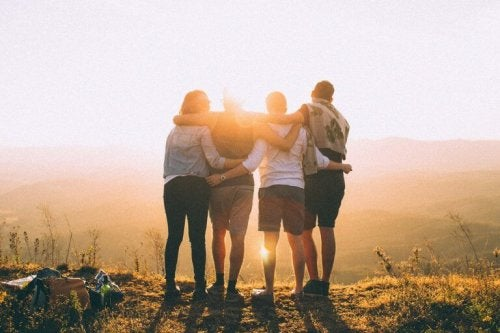 a group of people hugging each other on a mountain