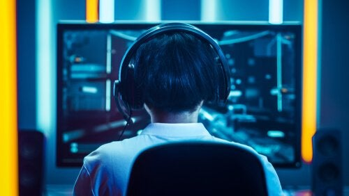 A boy with headphones on playing eSports.