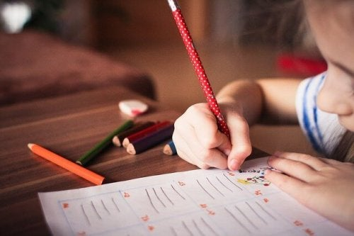 a little girl writing on paper with a pencil