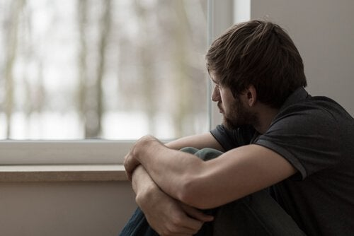A man sitting by the window, looking outside and looking sad.