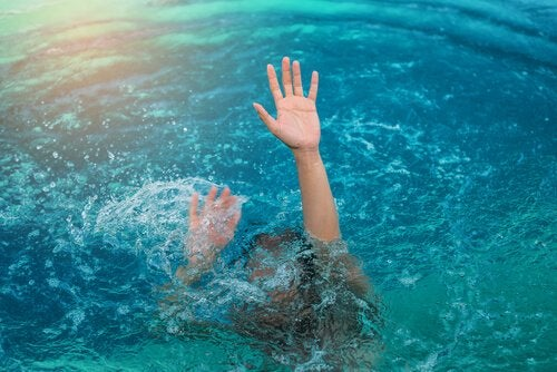 a person flailing in the water, with their head under and only their arms above