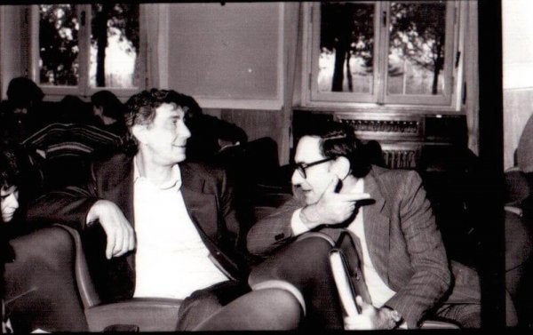 A photo showing Basaglia sitting in an armchair beside another man who's talking to him.