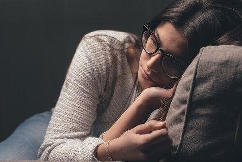 A sad woman lying down.