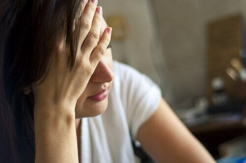 A close-up photo of a woman sitting down with her face in her hand out of sadness or frustration.
