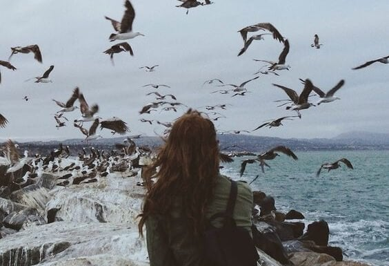 A woman surrounded by birds.