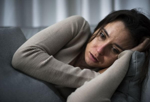 A woman lying on her couch looking extremely sad.