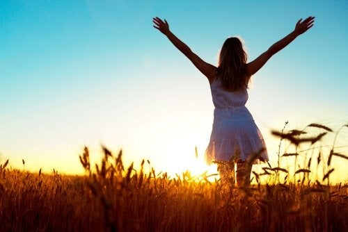 A happy woman standing in a field at sunrise, with her arms spread wide towards the horizon.