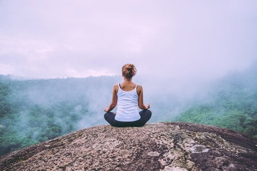 A woman meditating on a mountaintop.