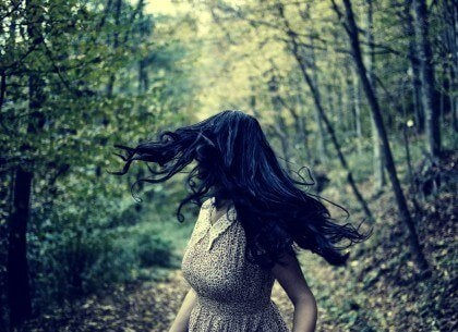 A woman running away from something in the woods.