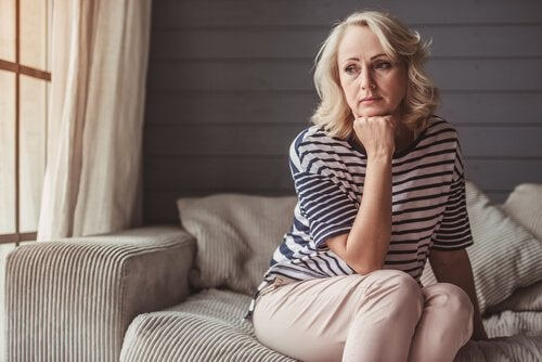 A woman sitting on a couch in her home, thinking about how to fight stagnation.