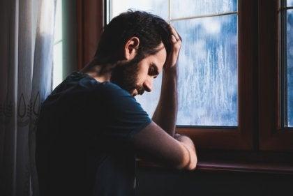 A sad man at a window.