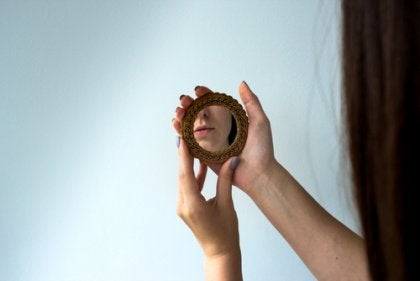 A woman looking into a hand mirror.
