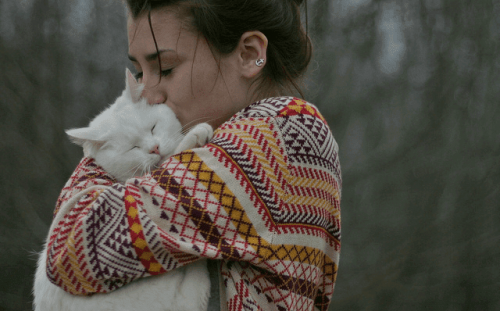 A woman hugging and kissing a cat.