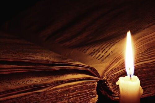 An open book by a candle light.