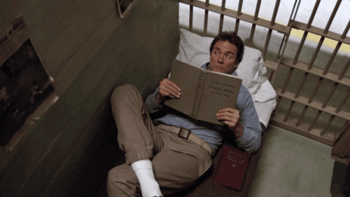 Frank Morris lying on a prison bed.