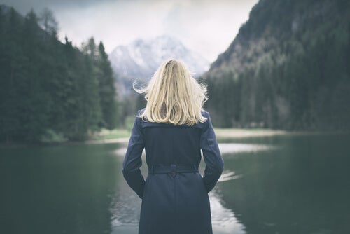 A blonde woman looking at the lake, from behind.